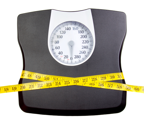 A bathroom scale with a measuring tape, weight loss concept